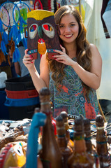 Young smiling beautiful woman holding in her hands a mask made of wood, in a store background