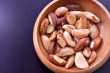 Close-up on a wooden bowl with Brazil nuts on black background
