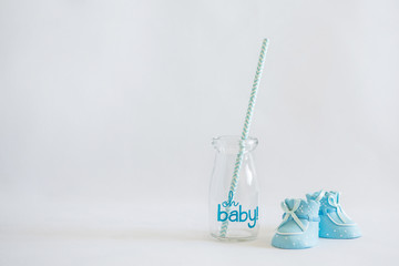 Decorative empty jar with straws and blue baby boy shoes