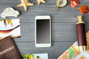 Composition with smart phone on wooden background. Travel apps concept
