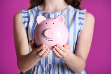 Young girl holding cute piggy bank in hands on pink background. Saving for education concept