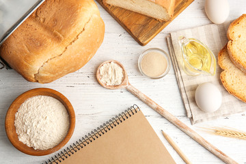 Composition with notebook and ingredients for bread on wooden table