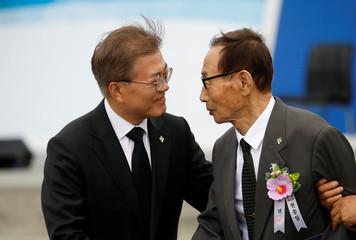 South Korean President Moon Jae-in helps a Korean War veteran during a ceremony marking Korean Memorial Day at the National Cemetery in Seoul