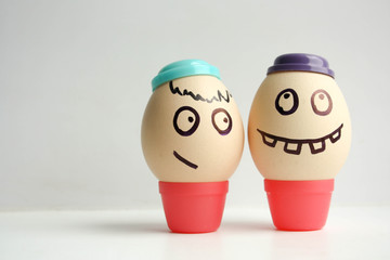Egg with painted face. Two eggs in caps
