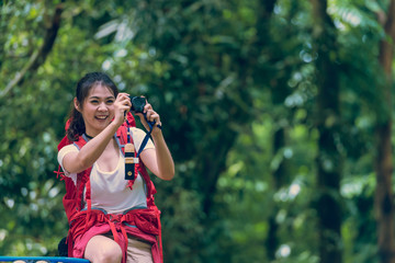 Beautiful young young woman with backpack taking photographs the beautiful landscape in forest at summer