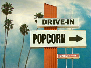 aged and worn vintage photo of drive in popcorn sign with palm trees