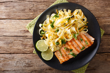 Pasta fetuccini with cheddar cheese and grilled salmon on a plate close-up. Horizontal top view