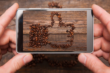 Social network. Mobile food photography. Thumbs up made by coffee beans. Popular shape for communication and advertisement on wooden background , top view