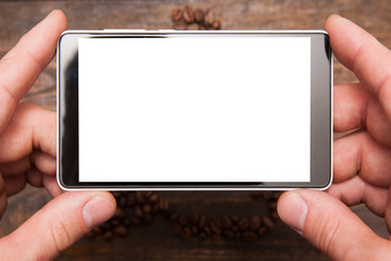 Mobile photography. Blank phone with touchscreen in hands on wooden background. White lcd screen top view, closeup.