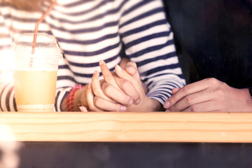 Young love couple holding hands together in the cafe in vintage color tone