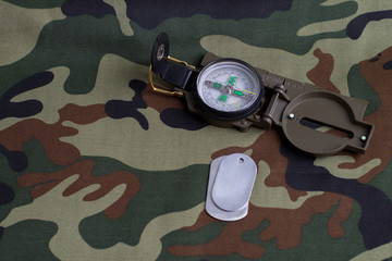 Army badge and compass on the background of camouflage