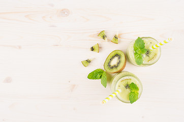 Foto op Plexiglas In het ijs Decorative frame of green kiwi fruit smoothie in glass jars with straw, mint leaf, cute ripe berry, top view. White wooden board background, copy space.