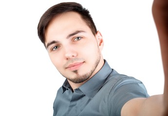 Handsome man making selfie and smiling. Picture of young cheerful man over white background standing while make a selfie by camera.