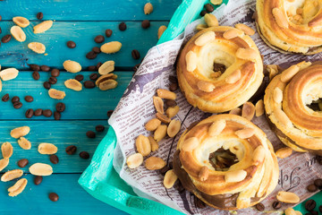Brewed ring with salted peanuts and chocolate-coffee cream on a turquoise background