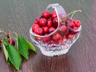 Freshly picked cherries in a crystal basket, with a branch of cherry tree with leaves and cherries still on