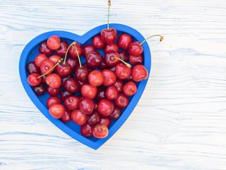 Freshly picked cherries on a blue heart shaped tray