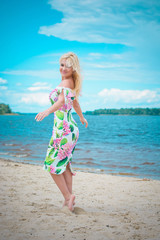 A beautiful girl on the coast near blue water enjoys the views of the sea of sun and beach. A woman on a good time is having a good time