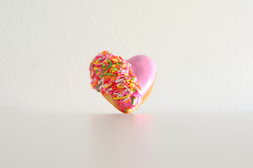Heart shape of donut covered by pink chocolate rainbow sprinkle decoration on isolate,Valentine day