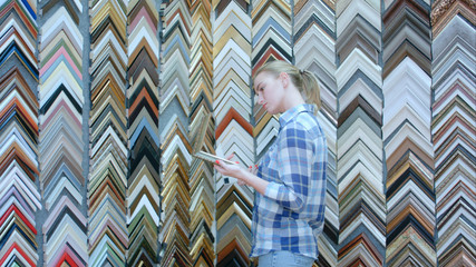 Portrait of young female customer looking for a frame, holding pieces in hands in special store