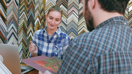 Cheerful female seller helping customer with frame and passepartout for his painting in store