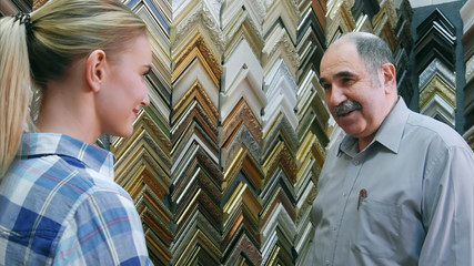 Joyful smiling senior man worker chatting with customer about frames in atelier