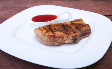grilled pork chop with Cranberry sauce on plate on wooden board
