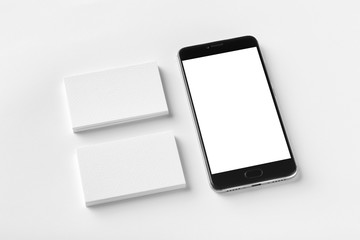 Mockup of two horizontal business cards and black cell-phone with blank screen at white textured paper background.