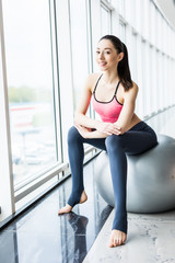 Beautiful young girl with fit ball. Fitness woman working out with pilates ball, relax and resting after workout