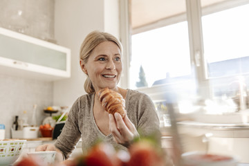 Woman at home eating a croissant