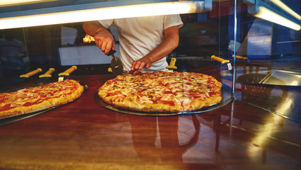 Food concept. Preparing traditional italian pizza. a man puts a fresh hot pizza on showcase in pizzeria. Ready to eat. Wall mural