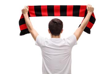 Rear view shot of teenage soccer fan holding scarf