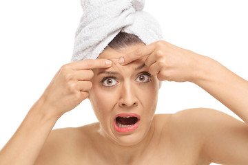 Shocked young woman squeezing a pimple on her forehead