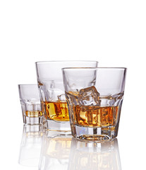 Three glasses of strong alcoholic drink scotch whiskey with ice cube