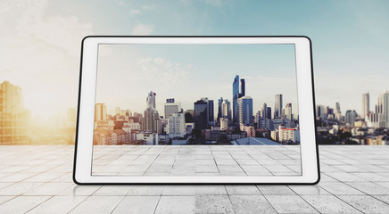 Digital tablet on white wood, with city backgrounds in sunrise