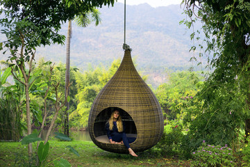 Scenic  view pf green forest with natural  hanging wicker swing in the drop shape design. Nice stuff for garden, park, patio and other outdoor places for recreation