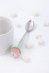 White cup with cubes of sugar and a spoon with a cake on a white background