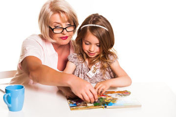 Grandmother and granddaughter reading a book on white background