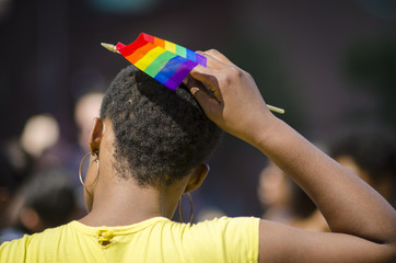 Young african-american woman place's rainbow flag in her afro hair and NYC's gay pride parade
