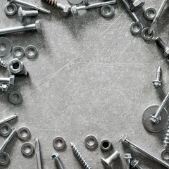 Construction tools. Frame made of screws, nuts and bolts on concrete background. Repair, home improvement concept. Top view, flat lay