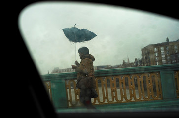 A woman struggles with her umbrella as she walks across Southwark Bridge on a wet and windy morning in London
