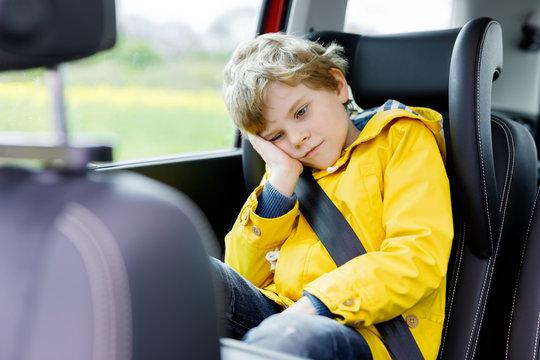 Tired preschool kid boy sitting in car during traffic jam