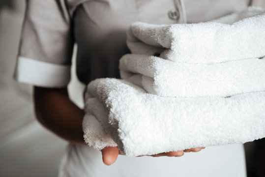 Close up of a young maid holding folded towels