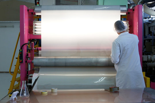 An employee works next to a device manufacturing plastic sheets at the production line of Israeli start-up Gauzy, in Tel Aviv