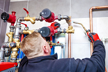 Plumber assembles the boiler room. Monter installs a central heating system.