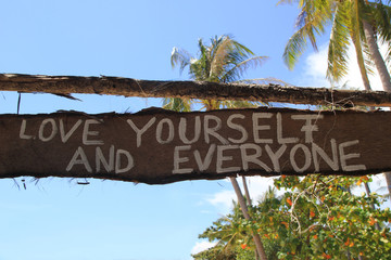 """Travel to island Koh Lanta, Thailand. Inscriptions """"Love yourself and everyone"""" on the wooden abandoned hut."""