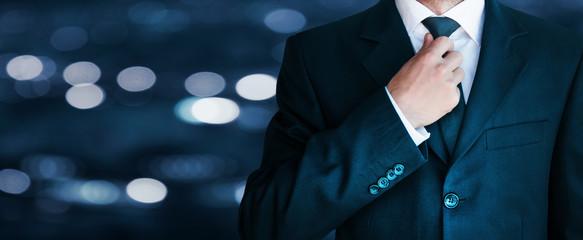Businessman in suit. He is fixing his tie.