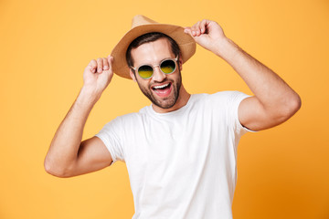 Happy young man standing isolated over yellow background