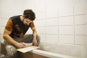A builder, tiler working in a bathroom, marking a tile with a pencil.