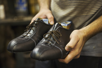 Close up of man standing in a shoemaker's workshop, holding a pair of handmade leather lace up cycling shoes.