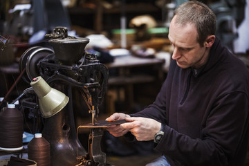 Man sitting at a large leather stitching machine in a shoemaker's workshop.